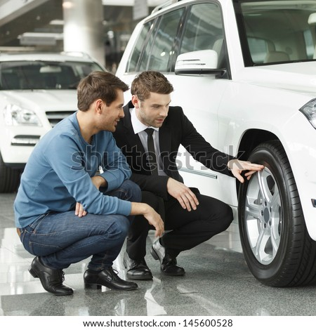 Look at these tires! Young car salesman showing the advantages of the car to the customer