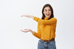 Look at this big thing. Excited smiling woman showing big object with hands on empty space, shaping box, sanding against white background.