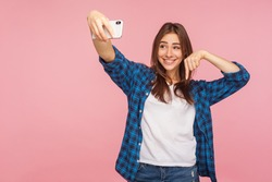 Look below, subscribe to channel! Portrait of happy blogger girl in checkered shirt smiling and pointing down, streaming to subs, having positive talk online. studio shot isolated on pink background