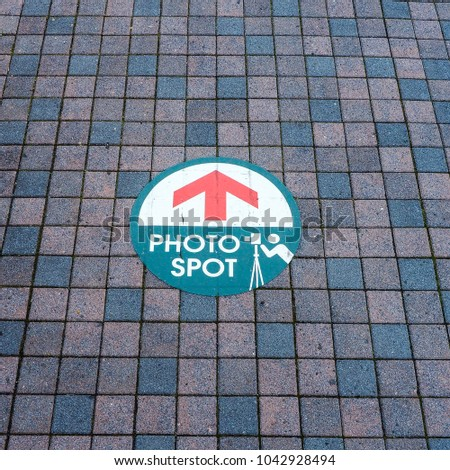 Look down at Japan footpath titles - Various color small rectangle block orderly align. With Photo Spot location sign. #1042928494