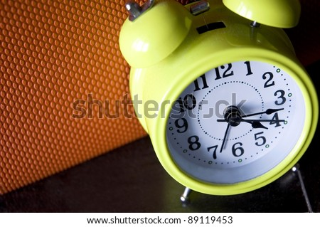 look down on green alarm clock with color background