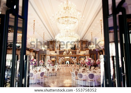 Look from afar at luxurious restaurant hall prepared for wedding dinner