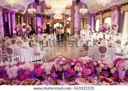 Look from behind dinner table decorated with garland of pink and white flowers at large dinner hall Сток-фото ©