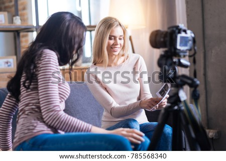 Look here. Delighted nice young woman sitting neat her friend and showing her pictures while preparing to shoot a video