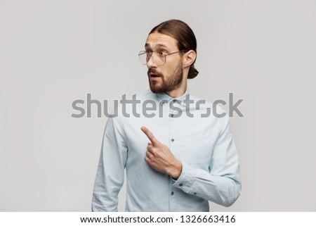 Look here left! Use this image for your website. Man pointing over grey studio background wall on copyspace for some information, advertising, logo. Lifestyle, emotional freestyle. Emotive feelings #1326663416