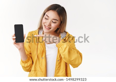 Look here my profile cool link. Attractive happy joyful asian blond female geek love technology new devices hold smartphone show display pointing looking phone screen discuss app white background