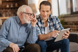 Look here. Pleasant young man pointing at the tablet, showing an interesting article to his elderly father while the man paying attention to him