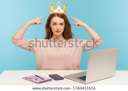 Look, I am boss here! Proud ambitious egoistic narcissistic businesswoman pointing at crown on head and looking with arrogance, over-inflated ego. indoor studio shot isolated on blue background Stock fotó ©