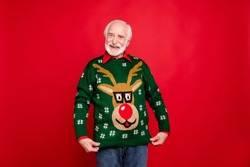 Look I got wonderful present! Portrait of positive cheerful funky old man show his theme christmas party sweater deer decor design wife gift have newyear celebration isolated red color background