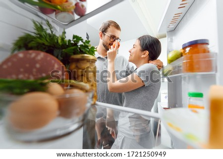 Look in the fridge. Young and successful couple in love looks in the fridge and take out of the fridge a bottle of milk while standing in the kitchen and makes breakfast.