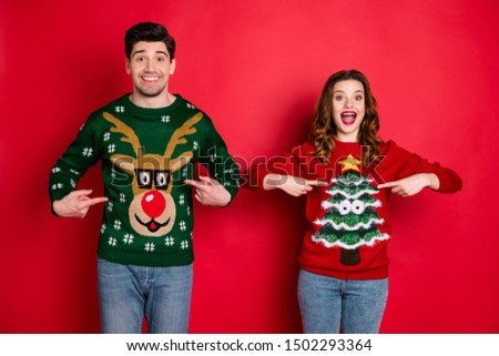 Look! Midnight presents! Portrait of two brunet hair  lovers people scream wow omg point indexf inger his her reindeer christmas tree pattern pullovers wear jeans isolated over red color background