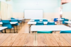Look out from the table, blur image of empty classroom as background.