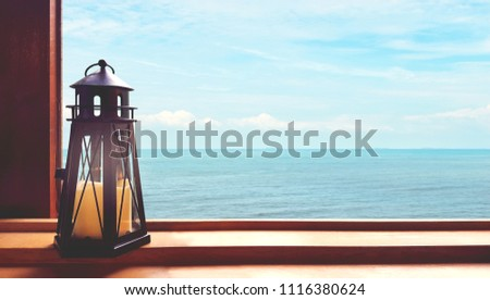 Look out the window, there is a candle (lighthouse shape) placed on the left side. Exterior overlooking the sea, sky and white clouds thinned far.  #1116380624