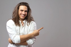 Look over there! Handsome cheerful man with long hair shows ad. Good looking smiling boy in studio. Space for your text or advertisement