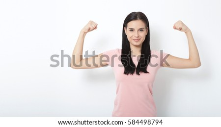 Look over there. Strong woman. Beautiful young woman showing her muscularity and looking at camera while isolated on white