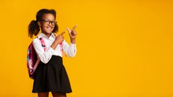 Look There. Black Elementary Student Girl Pointing Fingers At Copy Space Over Yellow Background. Panorama, Studio Shot