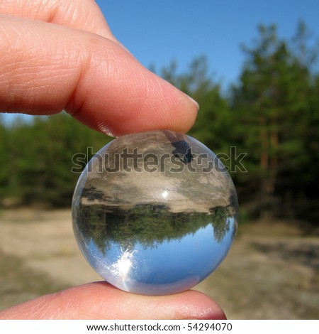 Look to inverted world through the crystal ball in fingers
