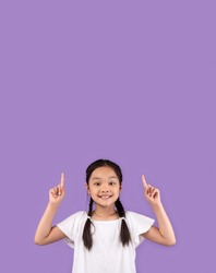 Look Up. Adorable Asian Kid Girl Pointing Fingers Upward At Copy Space Standing Over Purple Studio Background. Vertical