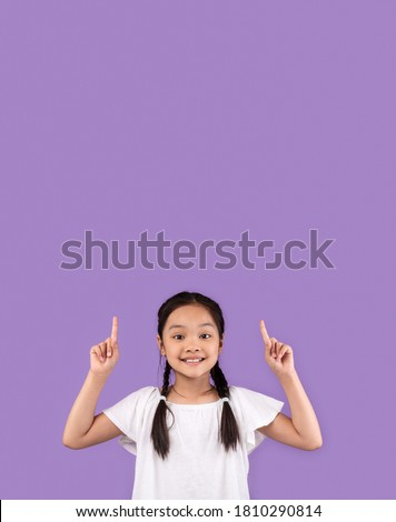 Look Up. Adorable Asian Kid Girl Pointing Fingers Upward At Copy Space Standing Over Purple Studio Background. Vertical Stock photo ©