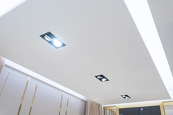 look up on suspended ceiling with halogen spots lamps and drywall construction in empty room in apartment or house. Stretch ceiling white and complex shape.