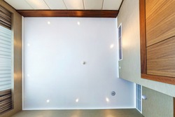 look up on suspended ceiling with halogen spots lamps and drywall construction with fire alarm sensor in empty room in apartment or house. Stretch ceiling white and complex shape.