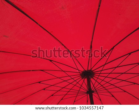 Look up under big red umbrella with black curves wire frames  #1034557147