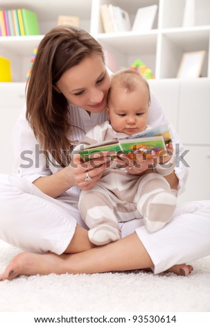 Look what a cute little ... woman and little girl watching a baby booklet