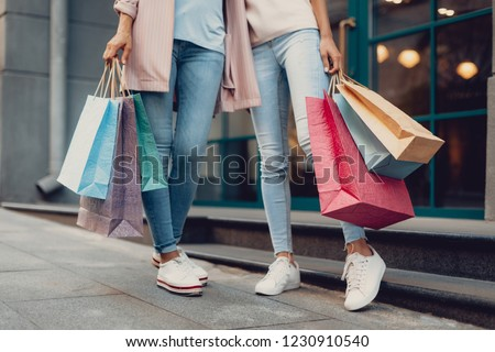 Look what we got. Cropped portrait of young lady and her mother holding colorful shopping bags