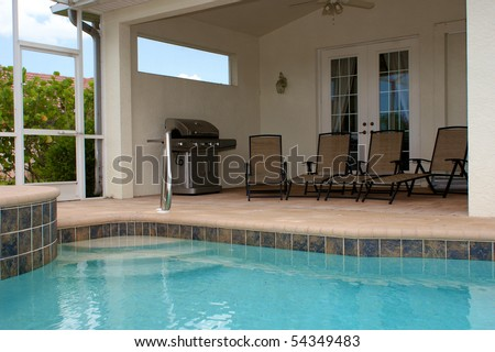 Looking Across A Large Built In Pool To A Sitting Are With Gas Grill And Four Lounge Chairs