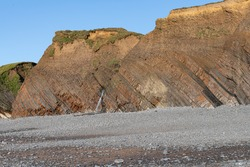 looking across pebbly beach to sedimentary rocks