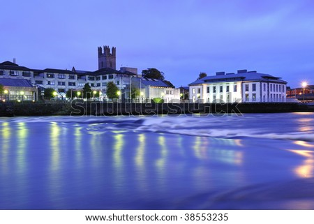 looking across River Shannon, towards Limerick City, Ireland. Slow shutterspeed gives water a smoothing effect while city lights give various colours