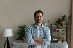 Looking ahead with confidence. Portrait of happy young male buyer of house flat standing at home in living room with arms crossed. Successful man owner of new apartment look at camera enjoy wellbeing