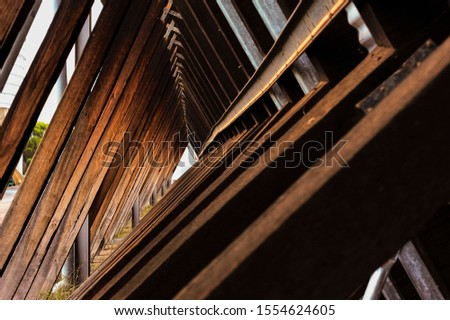 Looking along angled timber trusses and beams of a cantilever building, all converging at a true vanishing point.Creative composition of a timbered structure.
