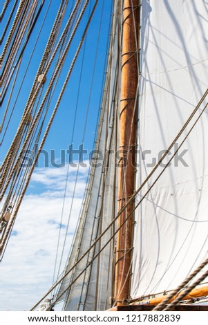 Looking at a mast, unfurled sail, and rigging of a 3-masted schooner on its way to the Island of Nicklösa in the Åland Islands, Finland.
