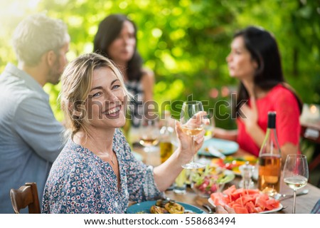 Looking at camera, portrait of a beautiful middle aged blond woman sharing a meal friends on a terrace table in summer, she has a glass of wine at hand. Shot with flare