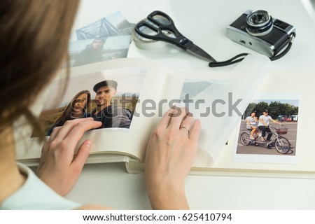 Looking at family wedding photo album. Young female engaged or married person turns pages and selects images for photo album #625410794