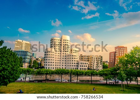 Looking at Media Harbor at Rhine-River in Dusseldorf in Germany. Media Harbor skyline among greenery of the city. Beautiful and colorful cityscape #758266534
