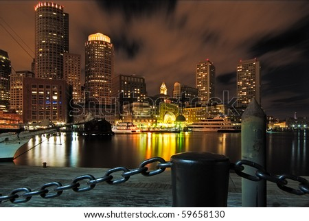 Looking back towards Boston fromRowe's Wharf at night with the city lighting up the sky