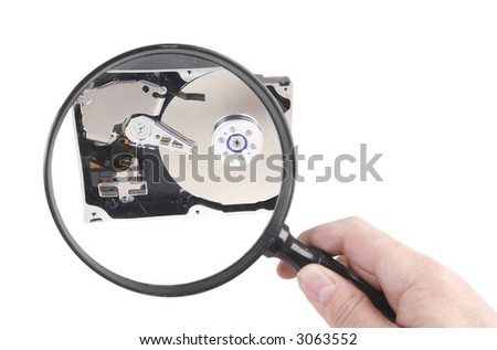 Looking closely at a hard drive with a Magnifying glass (concept)