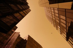 Looking directly up in the midle of glass corporate buildings, financial skyscrapers. In the middle of the sky a jet airplane crosses the business office towers in yellow golden. Modern, contemporary.
