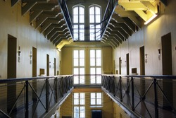 Looking down a deserted aisle lined on both sides with three levels of prison cells.