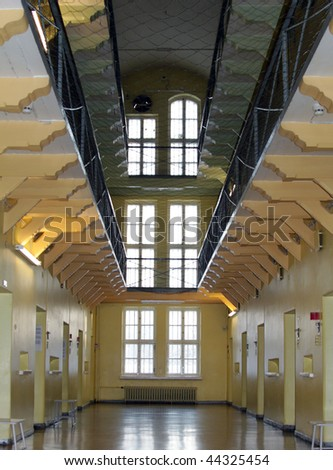 Looking down a deserted aisle lined on both sides with three levels of prison cells. - stock photo