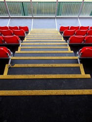 Looking Down a Flight of Stairs with Yellow Highlighted Stripes on the Outer Edge of the Steps, Leading to Seating Sections with a Platform and Railings.