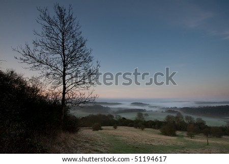 Looking down a hill towards some morning mist in the trees.  Taken just before dawn at Newlands Corner near Guildford in Surrey, UK.
