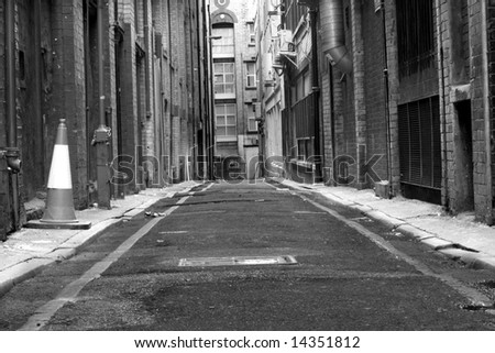 Looking down a long dark back alley - stock photo