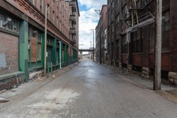 Looking down a vintage industrial street scene with classic red brick factories with metal fire escapes in a depressed urban area of St. Louis Missouri