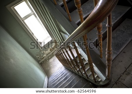 Looking down at an old wooden stairs at an abandoned building