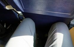 Looking down at narrow leg space in low cost airline seat, knees touching back rest at front