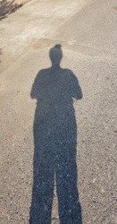 Looking down at the shadow of a woman on a concrete road, the shadow has long legs, a short body and high hair ties, making the shadow look funny and interesting. Standing in the sun creates a shadow.