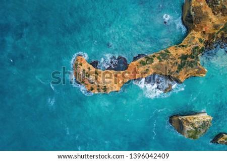 Looking down at turquoise ocean waves breaking over rocks - aerial view